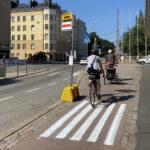 Väliaikaisen pysäkin raidat varoittavat pyöräilijää matkustajista